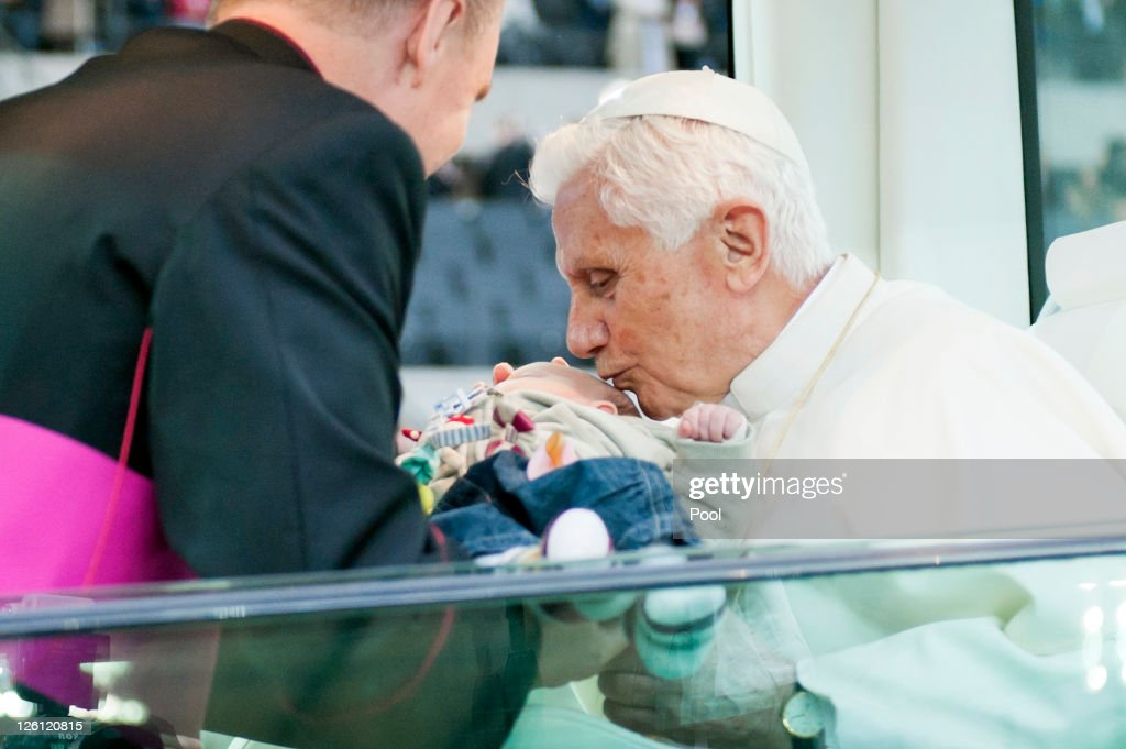 In this photo provided by the German Government Press Office private secretary Georg Gaenswein hands over a baby to Pope Benedict XVI during a Catholic mass for 70,000 visitors at Olympiastadion stadium on September 22, 2011 in Berlin, Germany. Pope Benedict, who is German, is in Berlin on the first of a four-day visit to Germany.