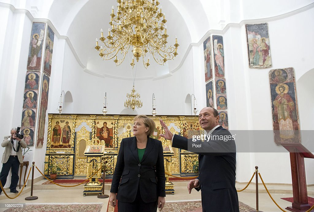 In this photo provided by the German Government Press Office, Romanian President <a gi-track='captionPersonalityLinkClicked' href=/galleries/search?phrase=Traian+Basescu&family=editorial&specificpeople=542324 ng-click='$event.stopPropagation()'>Traian Basescu</a> shows German Chancellor <a gi-track='captionPersonalityLinkClicked' href=/galleries/search?phrase=Angela+Merkel&family=editorial&specificpeople=202161 ng-click='$event.stopPropagation()'>Angela Merkel</a> art in the Orthodox Church on the ground of the Cotroceni Palace, the Romanian presidency headquarters, on October 12, 2010 in Bucharest, Romania.