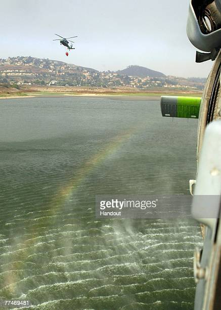 In this photo provided by the US Navy An MH60S Seahawk assigned to Helicopter Sea Combat Squadron 85 lifts a full 420gallon extinguishing trough from...
