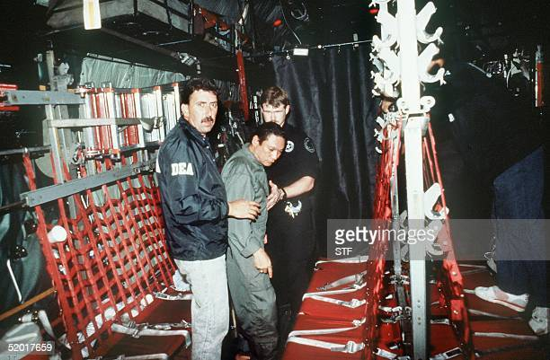 In this photo released 04 January 1990 by the Defense Department Panamian General Manuel Noriega is brought on board a US military plane 3 January...