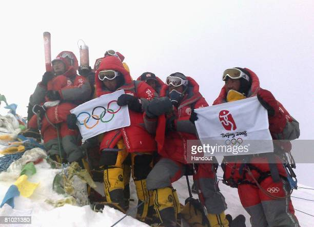 In this photo released by BOCOG Chinese climbers display an Olympic torch an Olympic flame lantern a flag of the International Olympic Committee a...