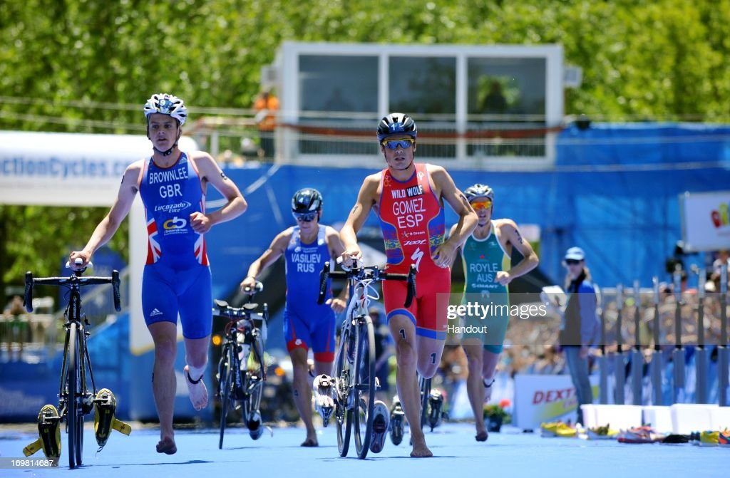In this photo released by the International Triathlon Union, Spain's Javier Gomez and Great Britain's <a gi-track='captionPersonalityLinkClicked' href=/galleries/search?phrase=Jonathan+Brownlee&family=editorial&specificpeople=5426331 ng-click='$event.stopPropagation()'>Jonathan Brownlee</a> run through transition at the ITU World Triathlon Madrid on June 2, 2013 in Madrid, Spain.