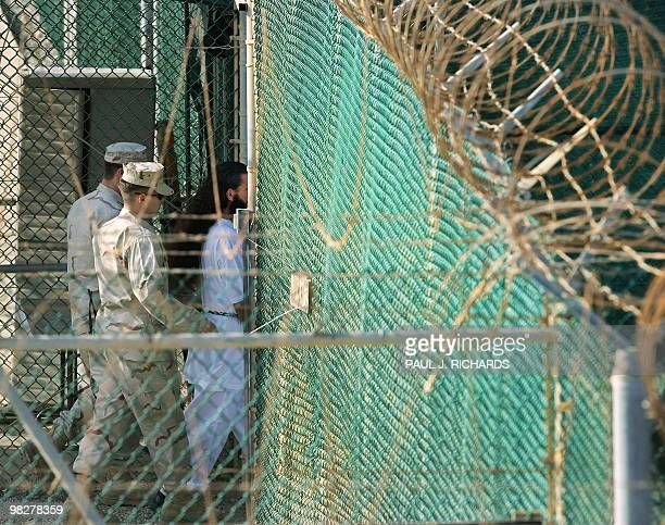In this photo reviewed by US military officials US military guards move a detainee to an undefined facility inside Camp Delta in the Detention Center...