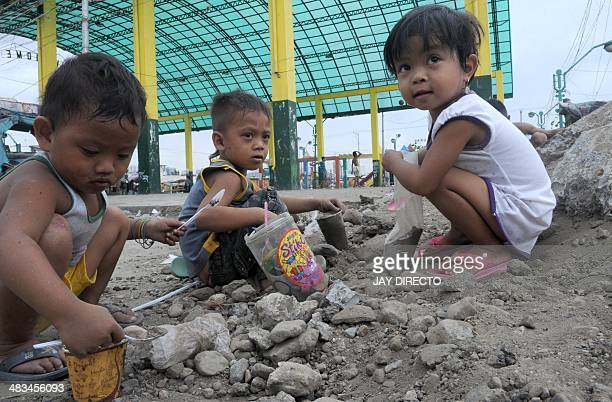 In this photo taken April 8 shows children in a slum playing in the dirt even as many of their mothers cite the need for greater help in family...