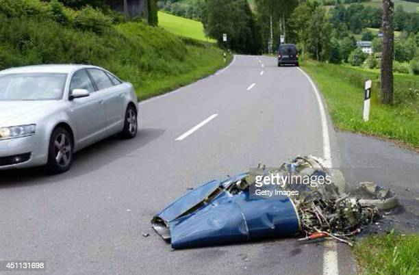 In this photo taken by a passerby with a mobile phone a car drives past wreckage from a Learjet that crashed following a collision with a Bundeswehr...
