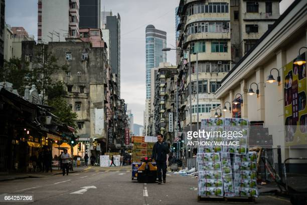In this photo taken early on March 16 a wholesale fruit vendor worker delivers fruit on a main road at the wholesale Yau Ma Tei fruit market in the...
