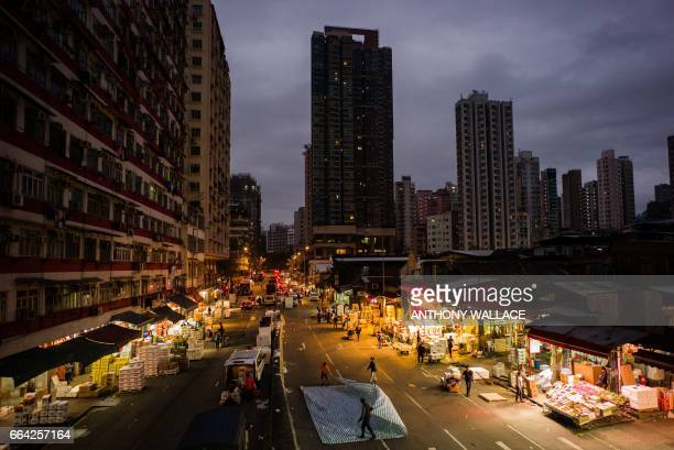 In this photo taken early on March 16 fruit vendors work on a main road at the wholesale Yau Ma Tei fruit market in the Kowloon district of Hong Kong...