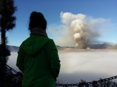 In this photo taken from Probolinggo in Indonesia's East Java province a woman watches as Mount Bromo spews ashes into the air during a volcanic...