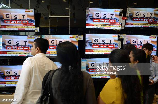 in this photo taken June 30 2017 Indians look at televisions displaying news on the new Goods and Services Tax regime at an electronic appliances...