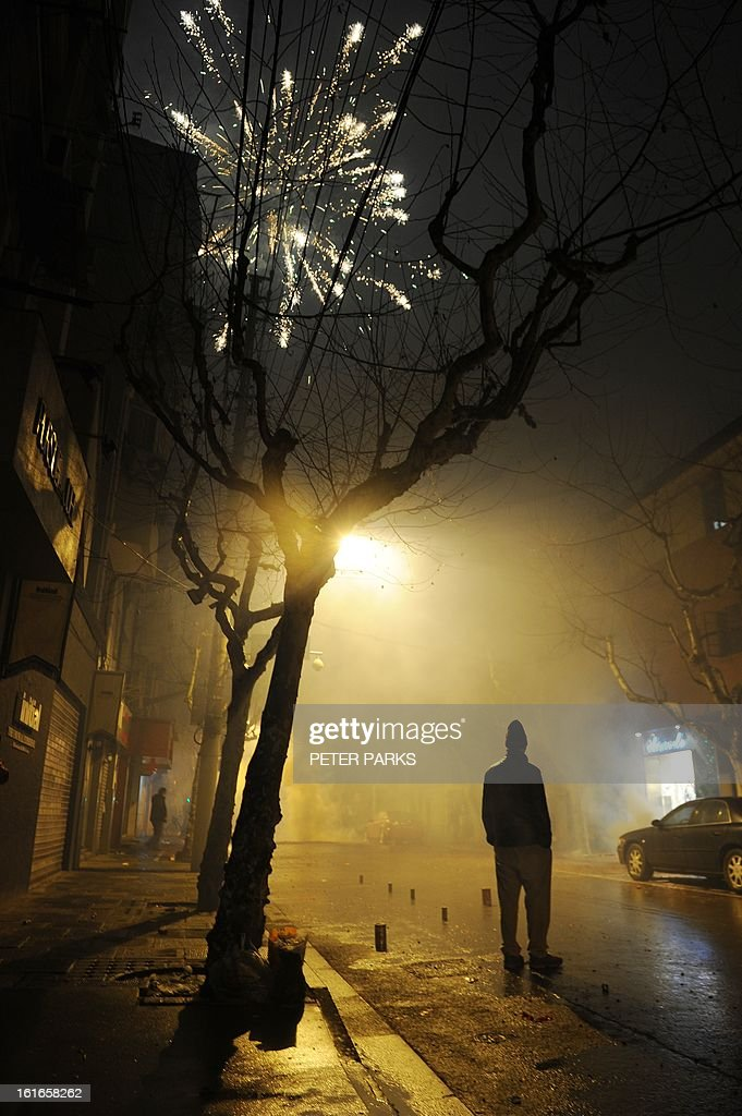 In this photo taken late February 13, 2013 people light fireworks on a street in Shanghai to celebrate the Lunar New Year. The Lunar New Year typically marks the largest annual movement of people as millions of people across China and other Asian countries squeeze into packed trains and buses to journey home to spend the season with their families. AFP PHOTO/Peter PARKS