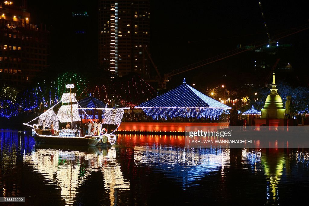 In this photo taken late on May 23 a decorated boat is seen in front of a lit Buddhist temple during Vesak celebrations in Colombo The Buddhist...