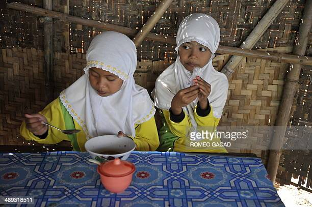 In this photo taken May 24 mud volcano victims Naila Himatulilliah and Alifia Fadina take their snacks in a canteen after their class in a temporary...