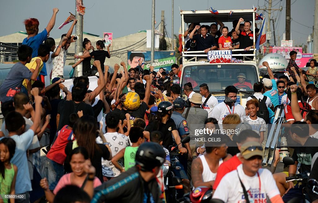 In this photo taken on April 27, 2016, A gathered crowd gestures as Philippine presidential candidate Rodrigo Duterte (centre L, in black) participates in a campaign motorcade near a port area in Manila. Rodrigo Duterte launched his profanity-laced campaign to become president of the mainly Catholic Philippines with a tirade against the pope that included branding the revered figure's mother a prostitute. Using such tactics -- which have drawn comparisons with US Republican Donald Trump and similarly upended conventional political wisdom -- Duterte has become the shock favourite to win Monday's election. / AFP / NOEL