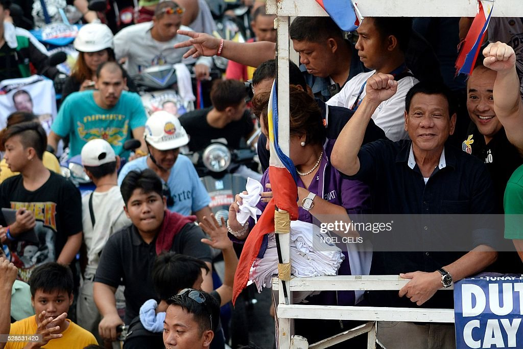 In this photo taken on April 27, 2016, Philippine presidential candidate Rodrigo Duterte (2nd R, in black) gestures to the crowd during a campaign motorcade near a port area in Manila. Rodrigo Duterte launched his profanity-laced campaign to become president of the mainly Catholic Philippines with a tirade against the pope that included branding the revered figure's mother a prostitute. Using such tactics -- which have drawn comparisons with US Republican Donald Trump and similarly upended conventional political wisdom -- Duterte has become the shock favourite to win Monday's election. / AFP / NOEL