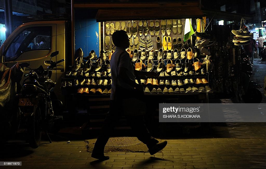In this photo taken on April 8, 2016, a Sri Lankan man walks past a roadside stall selling shoes in the Sri Lankan capital of Colombo. / AFP / ISHARA