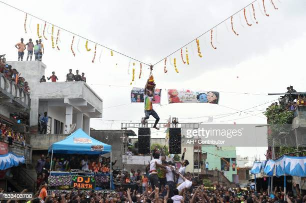 In this photo taken on August 16 2017 an Indian youth clings to a 'dahihandi' suspended in the air during celebrations for the Janmashtami festival...