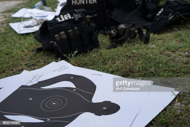In this photo taken on August 24 target sheets bulletproof vests and ammunition are seen on the ground as Thai police from the Narcotics Suppression...