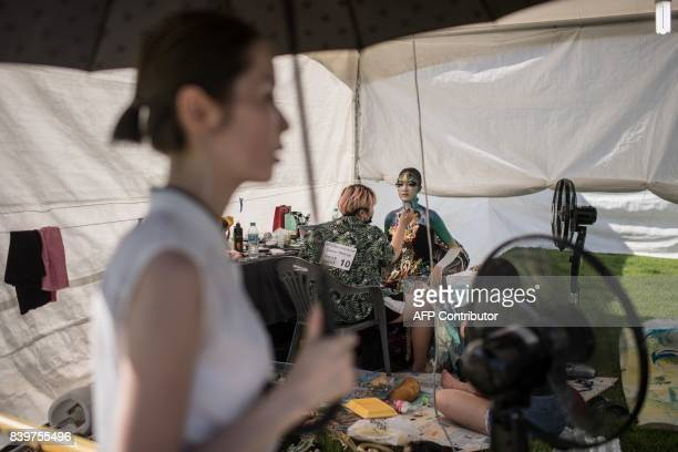 In this photo taken on August 26 a contestant applies designs to a model during the Daegu International Bodypainting Festival in Daegu The bodies of...