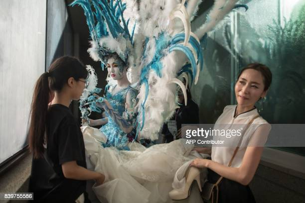 In this photo taken on August 26 a contestant of the 'fantasy' category prepares to be judged during the Daegu International Bodypainting Festival in...