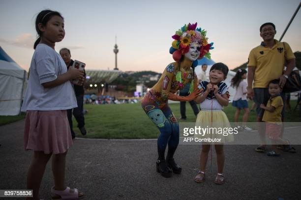 In this photo taken on August 26 a model poses for a photo during the Daegu International Bodypainting Festival in Daegu The bodies of dozens of...