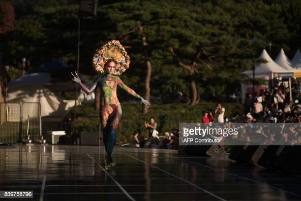 In this photo taken on August 26 a model poses on stage during the Daegu International Bodypainting Festival in Daegu The bodies of dozens of female...