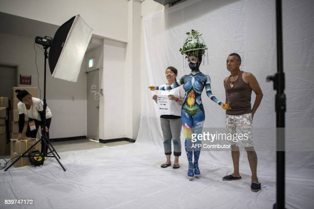 In this photo taken on August 26 contestant Aya Miyura of Japan stands with her model as they pose for a photo backstage before presenting themselves...