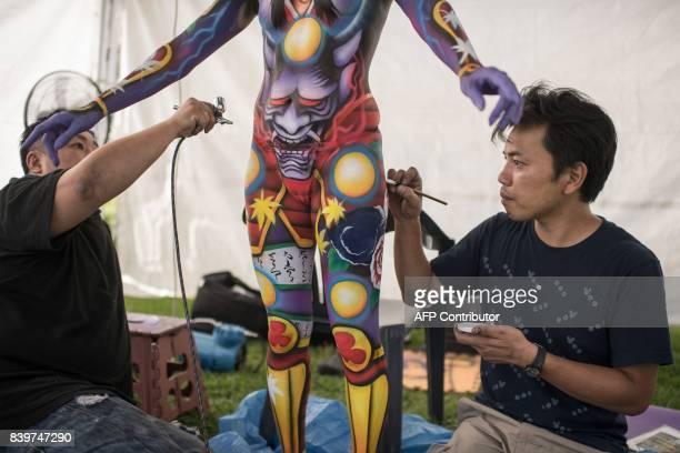 In this photo taken on August 26 contestant Iwasaki Masakazu of Japan applies his designs to a model during the Daegu International Bodypainting...