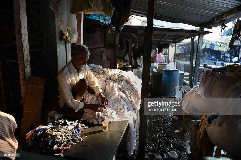 In this photo taken on December 11, 2012, an Indian worker removes thumbtacks from dirty party table aprons before someone else washes them at an open air laundry facility known as the Dhobi Ghat in Mumbai. This 25-acre (10-hectare) space is a chaotic conglomeration of rows of open-air concrete wash pens, each with its own flogging stone and rooms where the washermen, also known as 'dhobiwallahs', sleep and work. Many of the over 700 families that make a living out of this Dhobi Ghat, who had followed their father into the business, a life of dunking, thrashing and drying close to 1,000 items of clothing each day for just 7 USD, are worried about the future as the workload has gone down considerably. Most ordinary Indians who have seen their disposable incomes rise as the country's economy expands, have dispensed with the services of the dhobiwallahs for good since most modern homes are equipped with a washing machine. AFP PHOTO / Roberto Schmidt