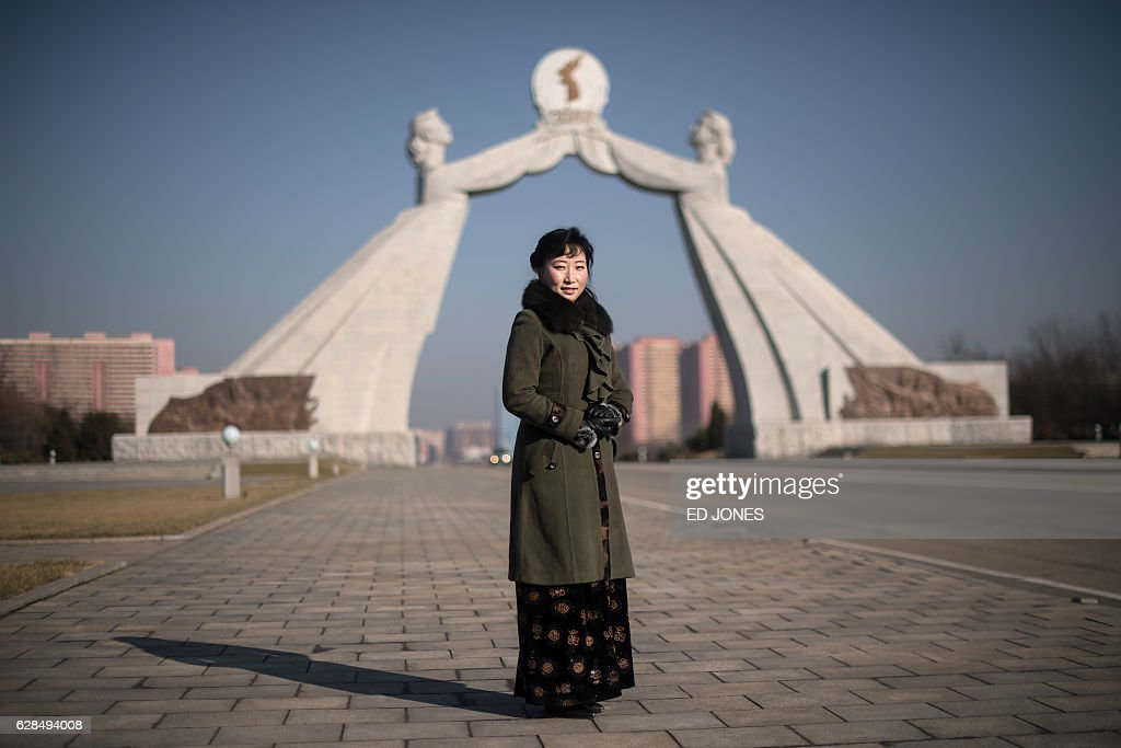 In this photo taken on December 2, 2016, tour guide Paek Hyon-Kyong (Baek Hyun-kyung) poses for a photo before the Three Charters of National Reunification Monument where she works on the outskirts of Pyongyang. / AFP / Ed JONES / This photo package is accompanied by a blog piece written by staff photographer Ed Jones https://goo.gl/lEZ8Fk