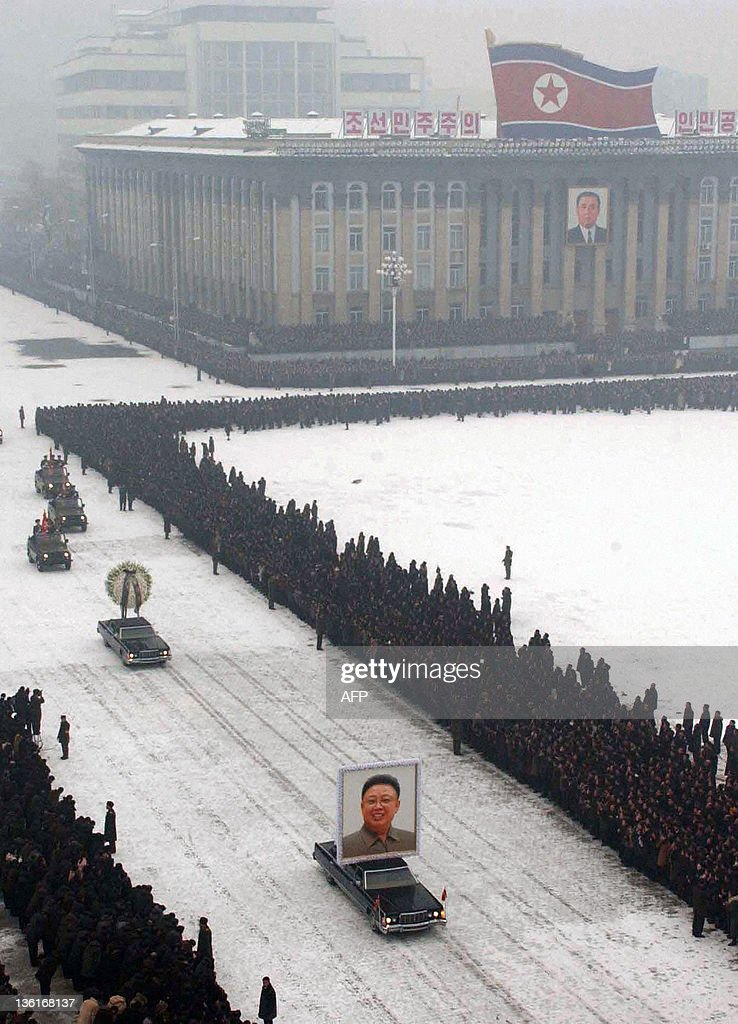 In this photo taken on December 28 2011 a car carries a portrait of Kim JongIl during the funeral procession in Pyongyang Millions of griefstricken...