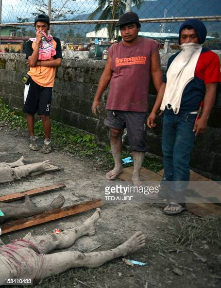 In this photo taken on December 5 2012 residents stand next to the bodies of victims of flash floods caused by Typhoon Bopha near the municipal hall...