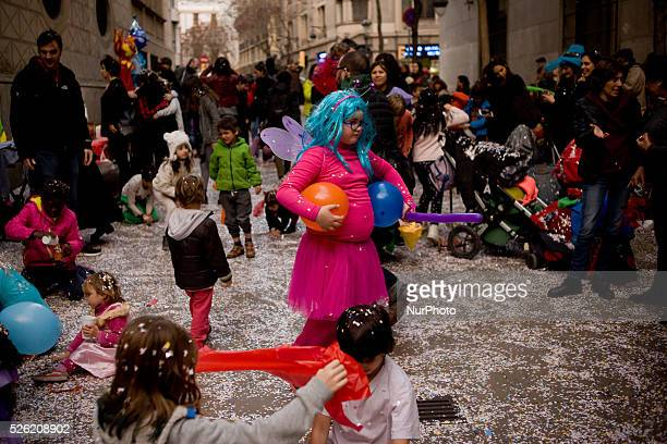 In this photo taken on Feb 5 Tania colorfully disguised holds two balloons while other children play with confetti during a carnival celebration...
