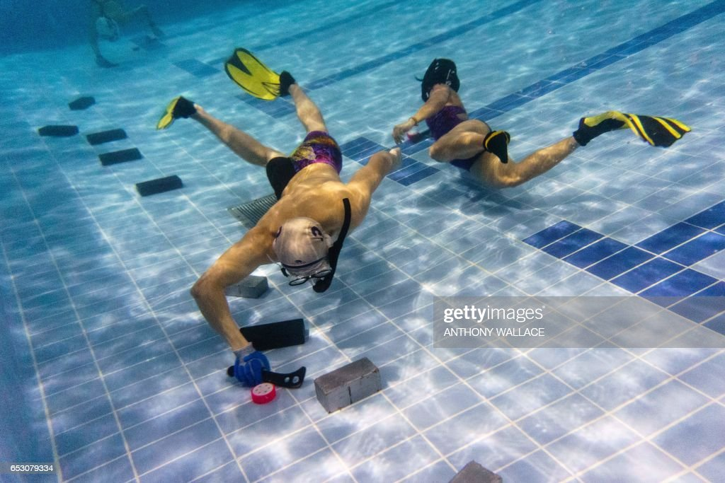 In this photo taken on February 15, 2017, members of the 'HK Typhoon' underwater hockey club take part in exercise drills during the team's once-a-week practise session at a 25-metre school pool in Hong Kong. The gravity defying sport of underwater hockey has gained a worldwide following -- now a Hong Kong team is diving in as the game takes off in Asia. / AFP PHOTO / Anthony WALLACE / TO GO WITH HongKong-sport-lifestyle-underwater-hockey,FEATURE by Aaron TAM