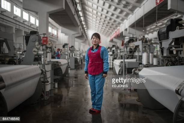In this photo taken on February 22 Kim JinHyang poses for a portrait at the Kim JongSuk textile mill in Pyongyang A regular fixture on the...