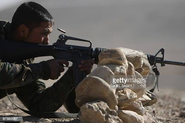 In this photo taken on January 13 an Afghan National Army trainee officer fires an M16 American assault rifle during training with the French army...