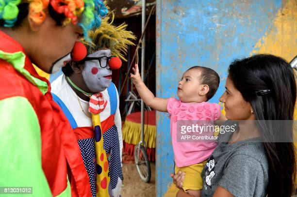 In this photo taken on July 11 Indian peformer Biju Nair meets a child in his clown costume during the Rambo Circus show in Bangalore The 26yearold...