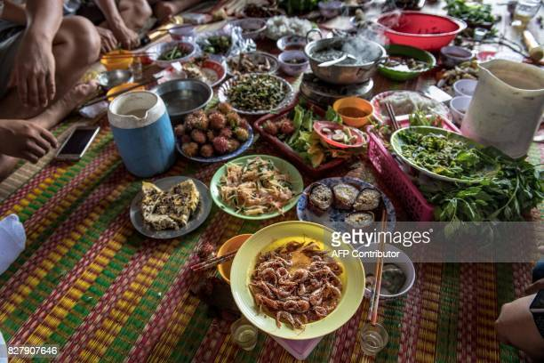 In this photo taken on July 13 a special meal is served on mats on the floor of a house belonging to a shrimp farmer as he and several others...