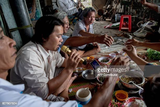 In this photo taken on July 13 shrimp farmers toast with rice wine as they celebrate the return of a family member from a successful trip to China...