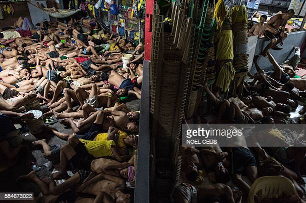 In this photo taken on July 21 2016 inmates sleep on the ground inside the Quezon City jail at night in Manila There are 3800 inmates at the jail...