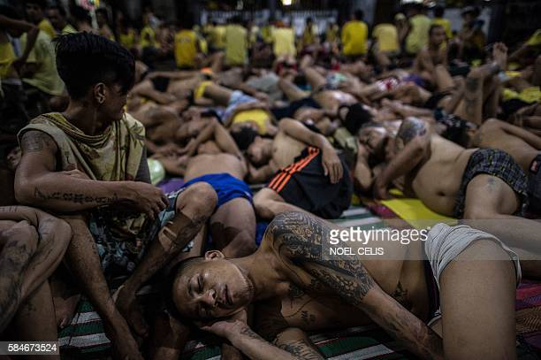 TOPSHOT In this photo taken on July 21 2016 inmates sleep on the ground inside the Quezon City jail at night in Manila There are 3800 inmates at the...