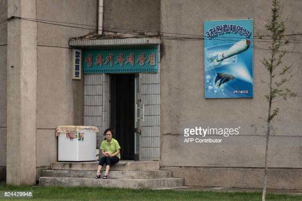 In this photo taken on July 23 a woman sits in a doorway before a poster showing a missile in Pyongyang North Korea said July 30 its latest ICBM test...