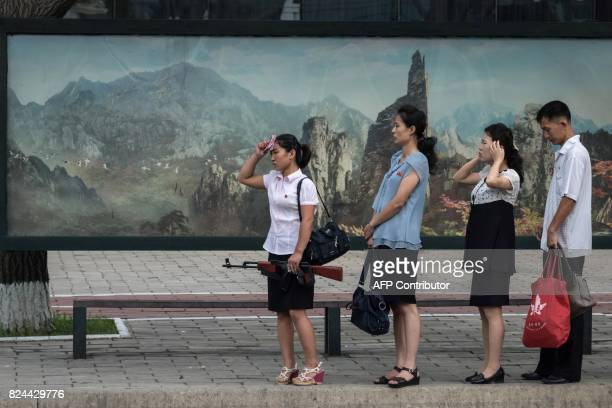 In this photo taken on July 29 a woman holding a mock rifle stands at a bus stop in Pyongyang North Korea said July 30 its latest ICBM test was a...