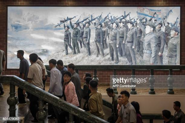 TOPSHOT In this photo taken on July 29 people walk up stairs before a propaganda poster showing Korean People's Army soldiers at a museum in Sinchon...