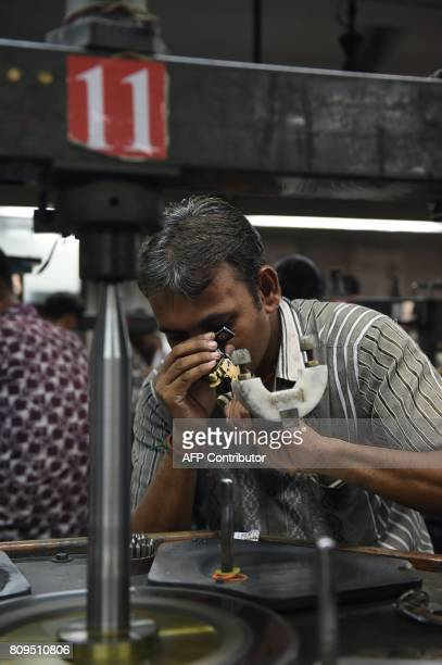 In this photo taken on July 5 an Indian worker examines a diamond at a diamond cutting and polishing unit in Ahmedabad The natural stones can take...