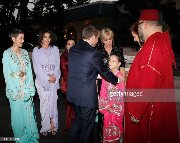 In this photo taken on June 14 2017 Morocco's King Mohammed VI and his daughter Lalla Khadija welcome welcome French President Emmanuel Macron and...
