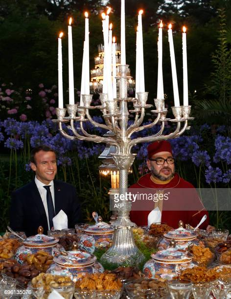 In this photo taken on June 14 2017 Morocco's King Mohammed VI and French President Emmanuel Macron taking part in an Iftar meal the evening meal...