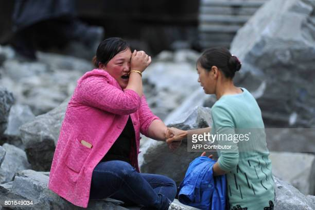 TOPSHOT In this photo taken on June 25 relatives mourn at the site of a landslide in Xinmo village Diexi town of Maoxian county Sichuan province...