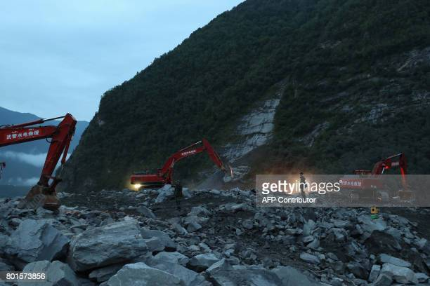 TOPSHOT In this photo taken on June 25 rescue workers are seen at the site of a landslide in Xinmo village Diexi town of Maoxian county Sichuan...