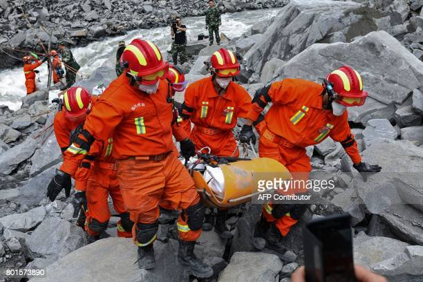 TOPSHOT In this photo taken on June 25 rescue workers carry the body of a victim on a stretcher at the site of a landslide in Xinmo village Diexi...