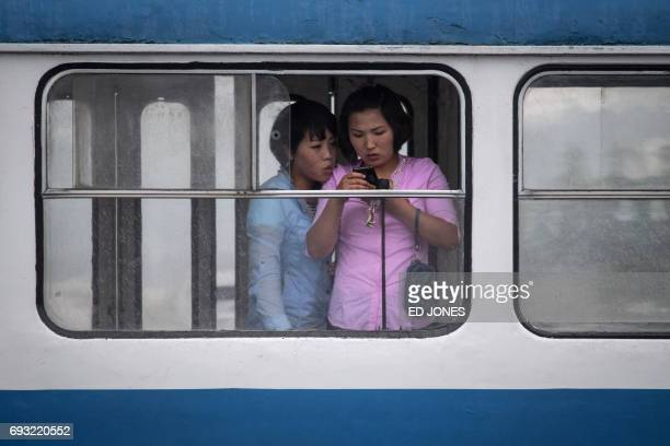 In this photo taken on June 6 women look at a mobile phone as they ride a tram in Pyongyang / AFP PHOTO / Ed JONES